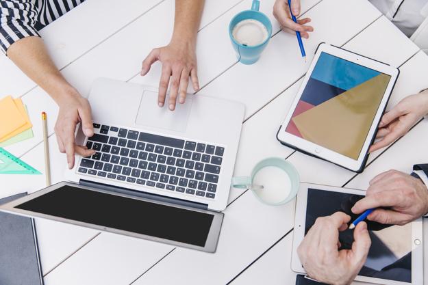 cortar-pessoas-usando-dispositivos-na-mesa-de-escritorio_23-2147787554